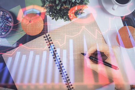 Forex chart hologram on hand taking notes background. Concept of analysis. Double exposure Reklamní fotografie
