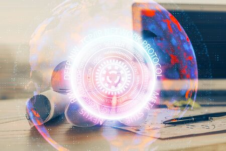 Computer on desktop in office with technology theme hologram. Multi exposure. Tech concept.