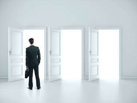Businessman with briefcase standing in white room with three open doors. Success and startup concept. Standard-Bild