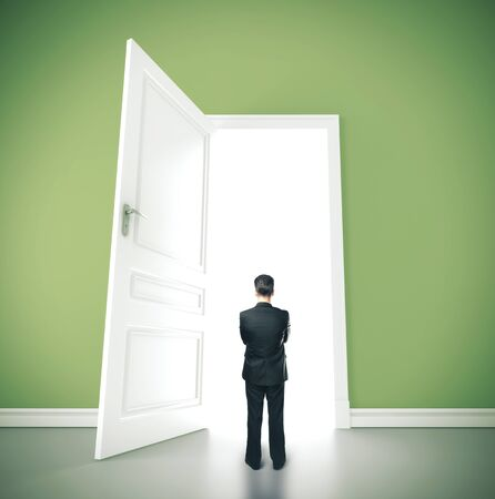 Businessman standing in green room with open doors. Success and startup concept. Standard-Bild