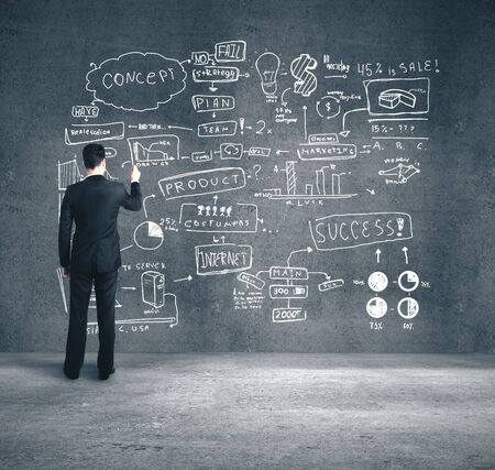 Businessman drawing business plan on concrete wall. Trade and business concept. Close up