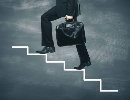 Businessman walking at drawing ladder on blackboard. Business and education concept.