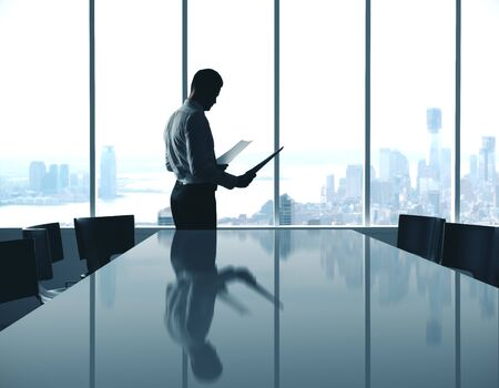 Biznesmen z dokumentem stojącym w nowoczesnej sali konferencyjnej z widokiem na miasto. Zdjęcie Seryjne