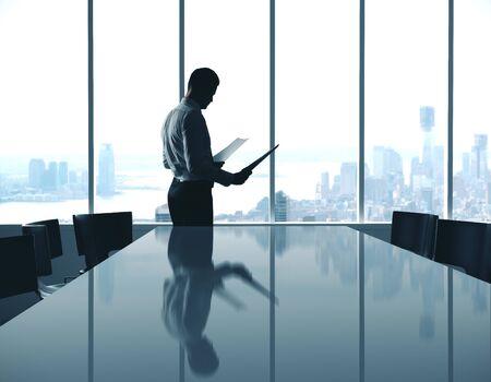 Empresario con documento de pie en la moderna sala interior de conferencias con vistas a la ciudad. Foto de archivo