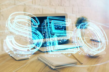 Multi exposure of table with computer and seo drawing hologram. Search optimization concept. Stock Photo