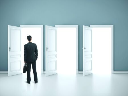 Businessman with briefcase standing in blue room with three open doors. Success and startup concept.
