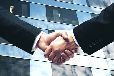 Businessmen shaking hands on modern skyscraper background. Teamwork and  business concept Banco de Imagens