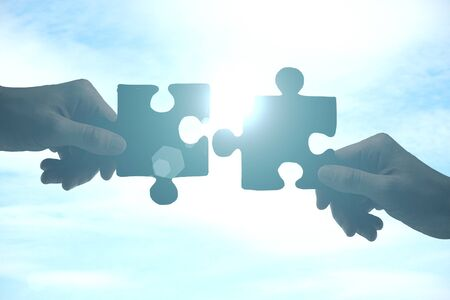 Hände, die Puzzleteile auf Himmelshintergrund mit Sonnenlicht zusammensetzen. Partnerschaftskonzept