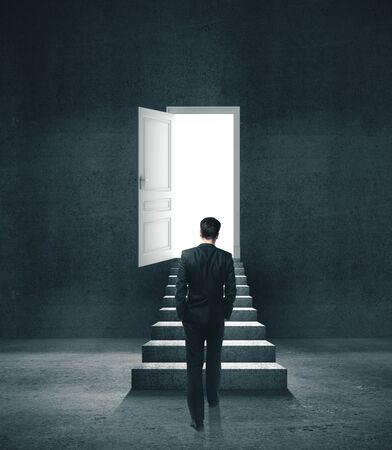 Businessman in concrete room walking to open door with light. Motivation and startup concept.