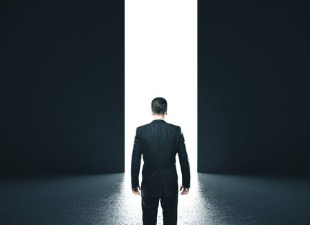 Businessman in concrete room with open door to light. Motivation and startup concept. Standard-Bild