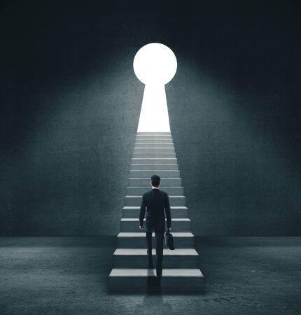 Businessman in concrete room walking to open door in form keyhole. Standard-Bild