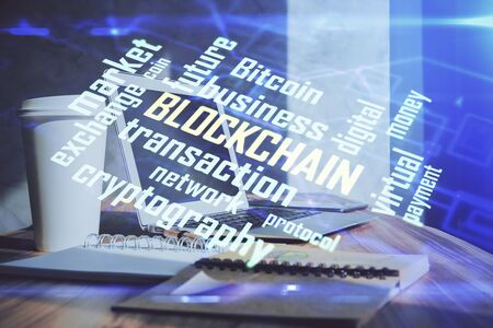 Double exposure of blockchain theme hologram and table with computer background. Concept of bitcoin crypto currency. 版權商用圖片