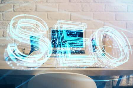Multi exposure of table with computer and seo drawing hologram. Search optimization concept. 版權商用圖片