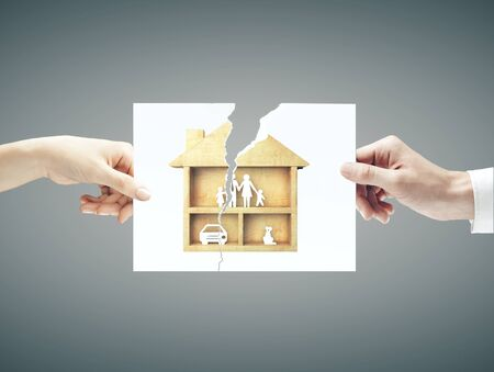 Hands hold torn sheet of paper with  family in wooden house on blue background. Family and comfort concept, Stockfoto