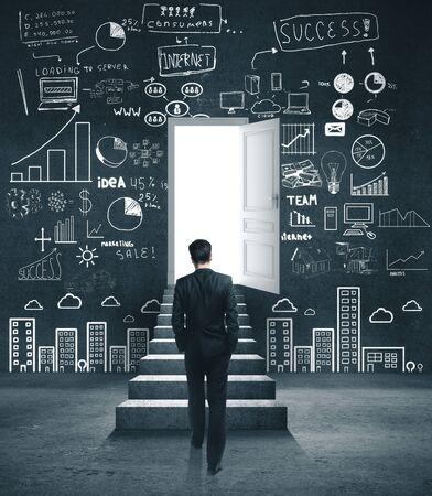 L'homme d'affaires monte les escaliers. Dessin d'esquisse d'entreprise sur un mur en béton. Concept de réussite et de démarrage.