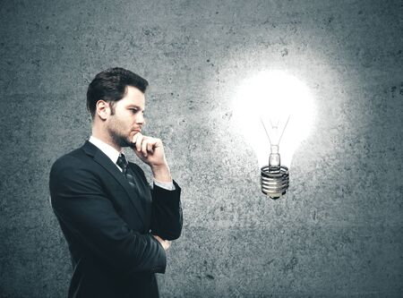 Businessman looking on glowing lamp Success and startup concept.