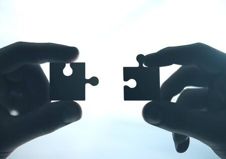 Hands putting puzzle pieces together. Close up. Business and challenge concept.