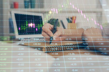 Financial graph displayed on womans hand taking notes background. Concept of research. Double exposure Standard-Bild