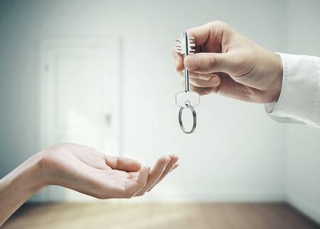Hand puts the key to the new house on a interior room  background. Business and success concept.