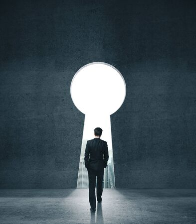 Businessman walking to opened concrete wall in form keyhole. Business and security concept.