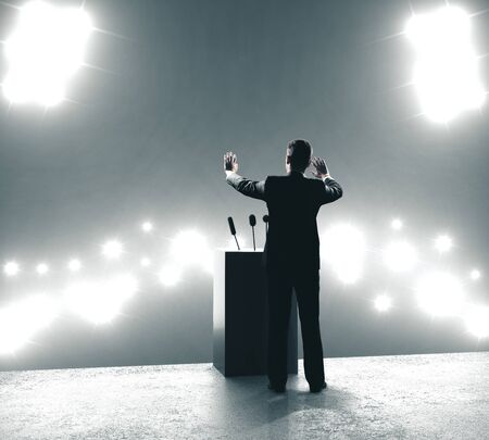 Businessman giving speech in backlit audience. Business and leader concept
