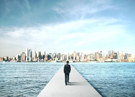 Businessman walking to modern city on concrete bridge. Business and challenge concept.