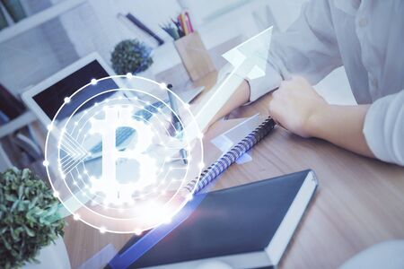 Cryptocurrency hologram over hands taking notes background. Concept of blockchain. Multi exposure