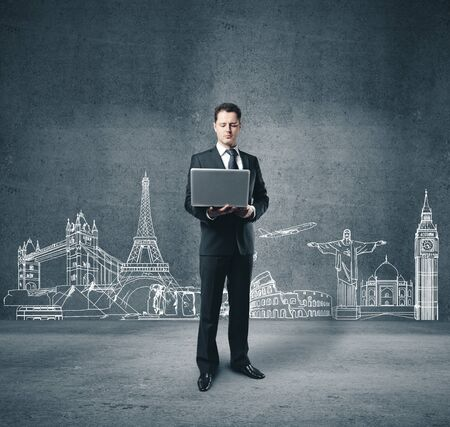 Businessman with notebook and drawing monuments of architecture on concrete wall. Travelling concept