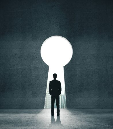 Businessman looking to opened concrete wall in form keyhole. Business and security concept.