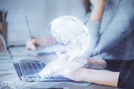 Double exposure of woman hands working on computer and world map hologram drawing. International technology business concept.