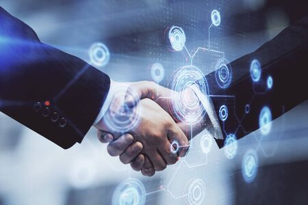 Double exposure of data theme hologram and handshake of two men. Partnership in IT industry concept. Imagens