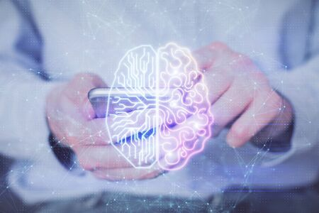 Double exposure of mans hand holding and using a digital device and brain hologram drawing. Data concept.