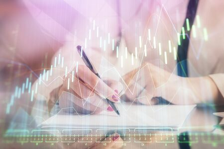 Double exposure of hands making notes with forex chart huds. Stock market concept. 版權商用圖片