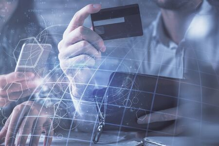 Double exposure of man and woman on-line shopping holding a credit card and map hologram drawing. International E-commerce pay on-line concept.