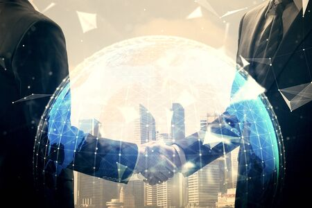 Double exposure of business theme hologram and handshake of two men. Success concept.