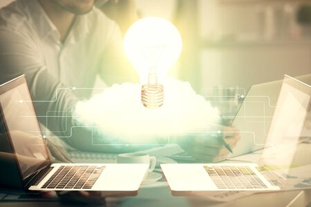 Double exposure of man and woman working together and light bulb hologram drawing. Idea concept. Computer background.
