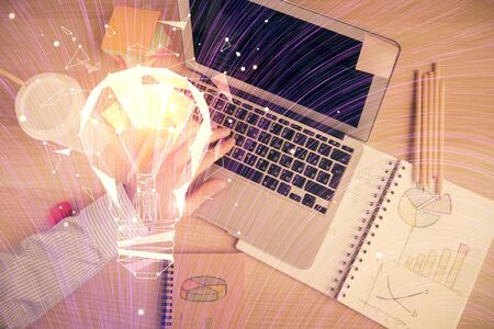 Double exposure of man's hands typing over computer keyboard and bulb hologram drawing. Top view. Idea concept.
