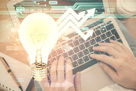 Double exposure of mans hands typing over computer keyboard and bulb hologram drawing. Top view. Idea concept.