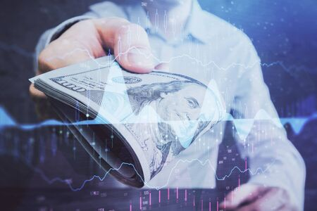 Multi exposure of financial graph drawing hologram and USA dollars bills and man hands.