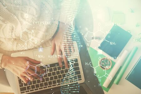 Double exposure of woman hands working on computer and DNA hologram drawing. Top View. Medical education concept.