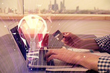 Double exposure of man hands holding a credit card and bulb drawing. Idea E-commerce concept.