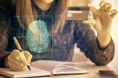Multi exposure of woman on-line shopping holding a credit card and finger print drawing. Security concept.