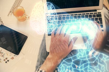 Double exposure of mans hands typing over computer keyboard and virtual reality hologram drawing. Top view. Technology concept. Future.