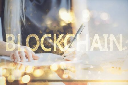 Cryptocurrency hologram over womans hands writing background. Concept of blockchain. Double exposure