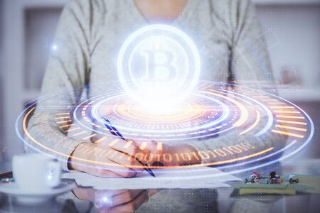 Cryptocurrency hologram over womans hands writing background. Concept of blockchain. Multi exposure