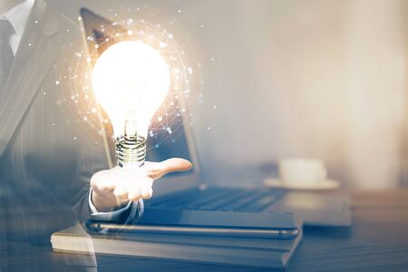 Computer on desktop in office with bulb icon hologram. Multi exposure. Concept of idea. Banco de Imagens