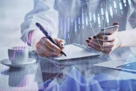 Double exposure of financial graph sketch hologram and woman holding and using a mobile device. Stock exchange concept.
