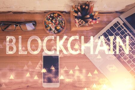Double exposure of blockchain theme hologram over table with phone. Top view. Crypto technology concept.