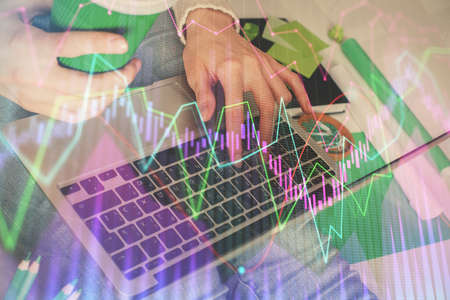 Double exposure of woman hands typing on computer and forex chart hologram drawing. Stock market invest concept. 免版税图像
