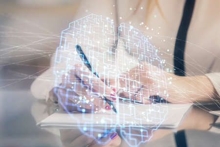 Multi exposure of womans writing hand on background with brain hud. Concept of learning. Фото со стока